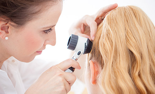Doctor inspecting patient Scalp with a Dermatoscope
